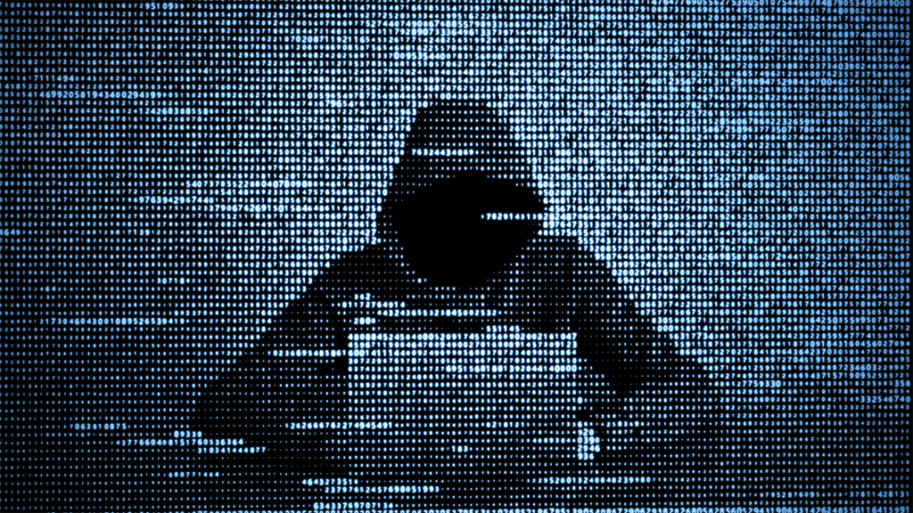 An image of a hacker wearing a sweatshirt that obscures his face