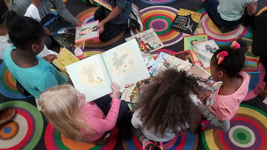 overhead shot of children reading books on a rug