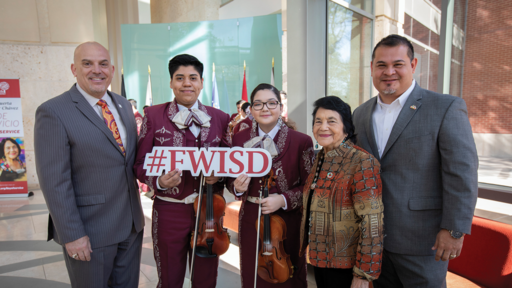 "Jacinto Ramos and a group of people including students hold a ""#FWISD"" sign and smile for the camera"