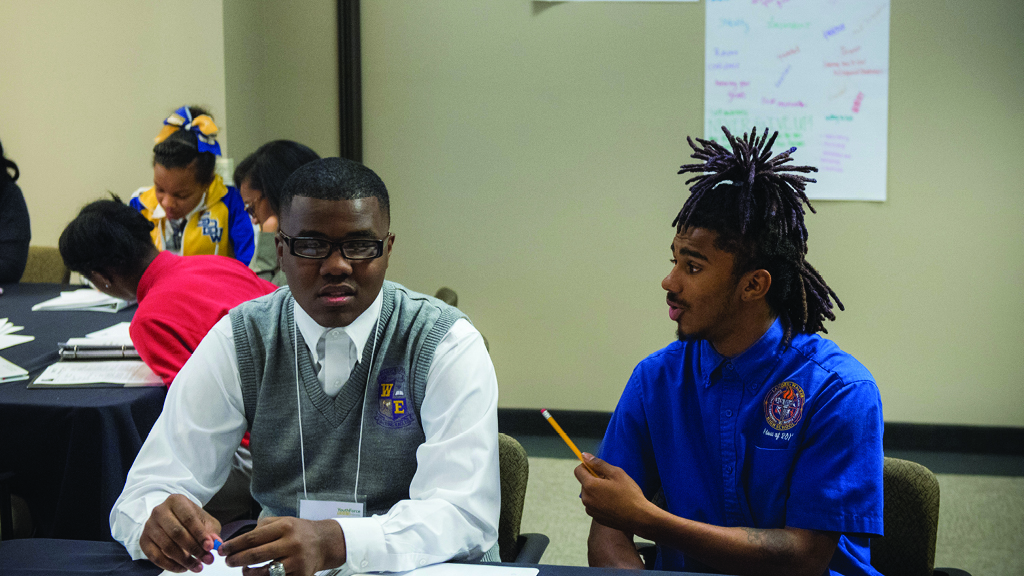 Two students sit at a desk and talk