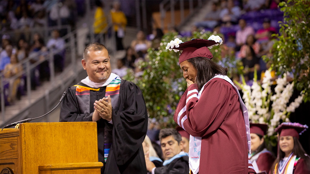 Jacinto Ramos on stage with a student graduating