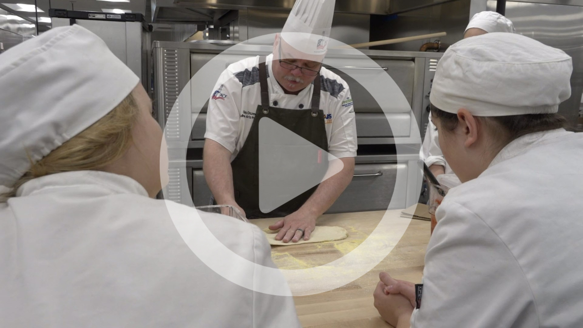 "An instructor teaches culinary students with a ""play"" button"