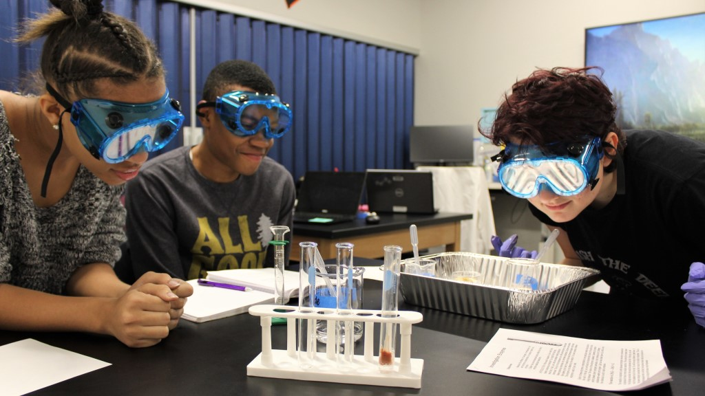 Three students look at test tubes while wearing safety glasses