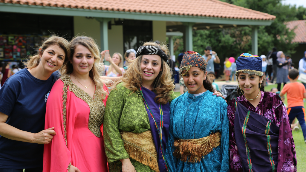 Students in their cultural dress smile at the camera