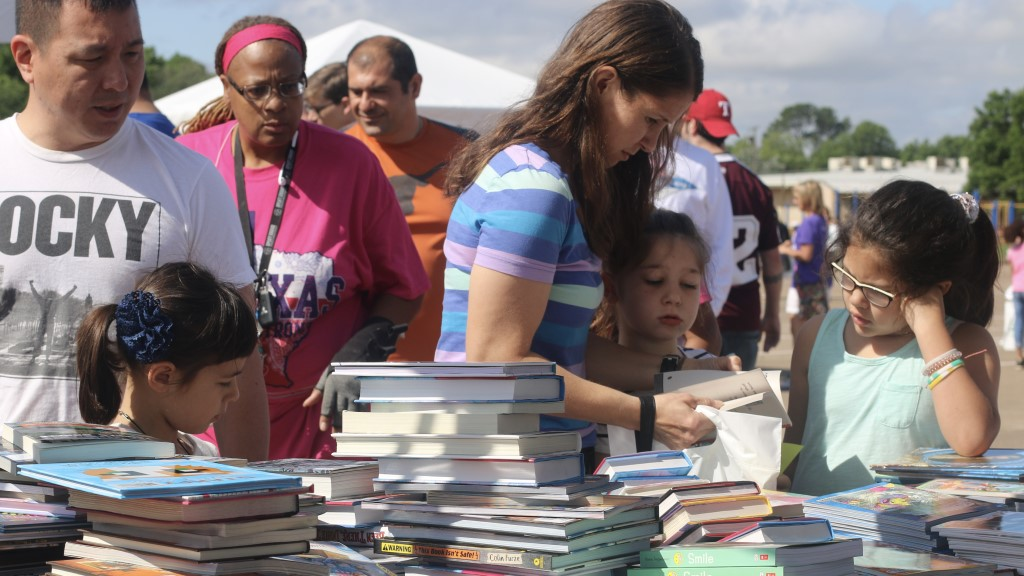 Students and their families pick books out from several large stacks