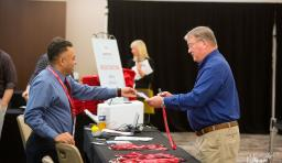 An NSBA staff member hands over registration materials to a conference attendee