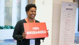 "a conference attendee holds up a sign that says ""NSBA4IDEA"""