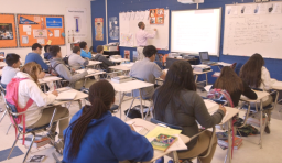 a picture from the back of a classroom. students look at their teacher who is writing on the whiteboard