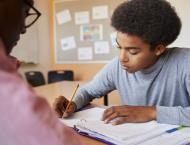 a boy being tutored at a desk