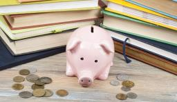 an image of a sad looking piggy bank with coins scattered around it. there are school books in the background