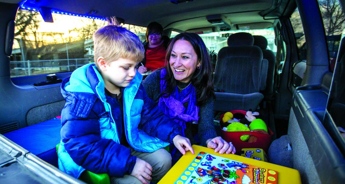 A child and adult playing an educational game inside a van